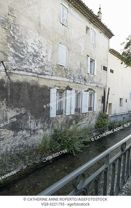 Crumbling, distressed plaster work and tiered roof tiles on ancient buildings lining the clear streams of the River Sorgue from behind a balcony in...