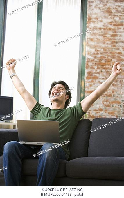 Young man cheering with laptop