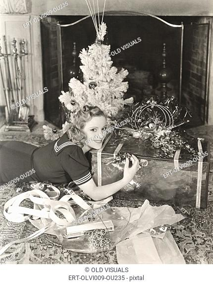 Woman lying on floor by Christmas gift and tree at home