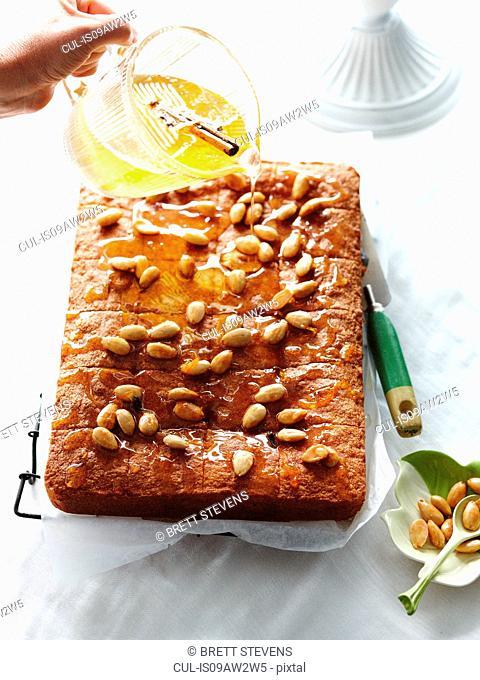 Pouring syrup on almond semolina cake
