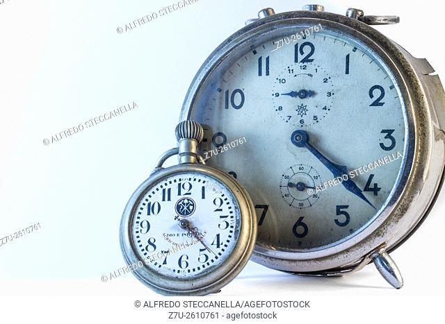 An old rusty alarm-clock with a pocket clock on white background