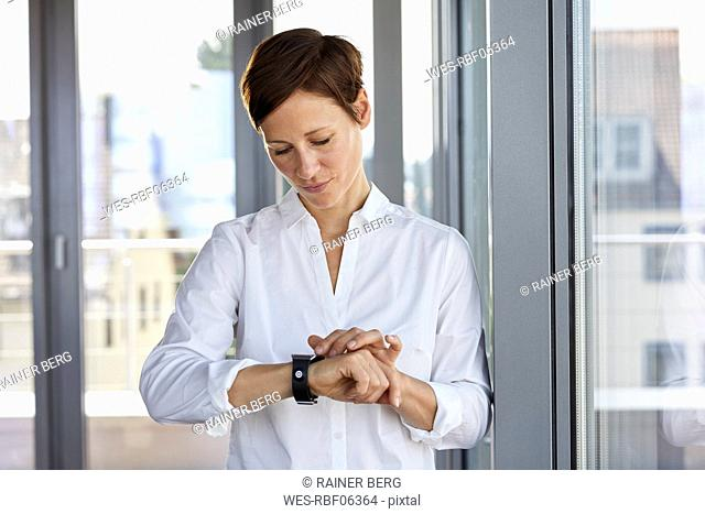 Businesswoman at the window in office checking the time