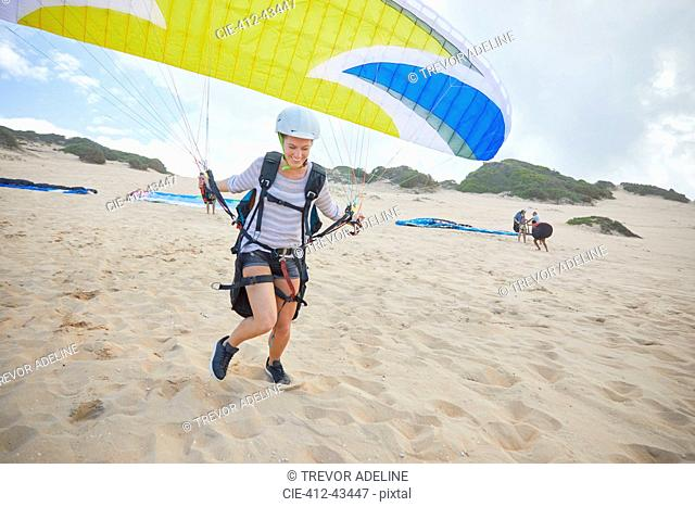 Female paraglider with parachute running, taking off on beach