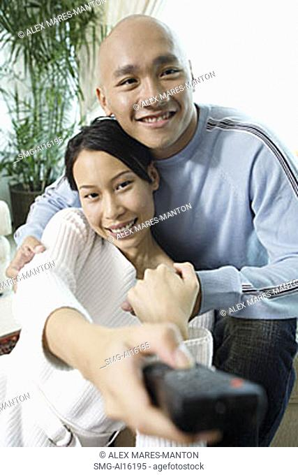 Couple in living room, woman holding remote control forward