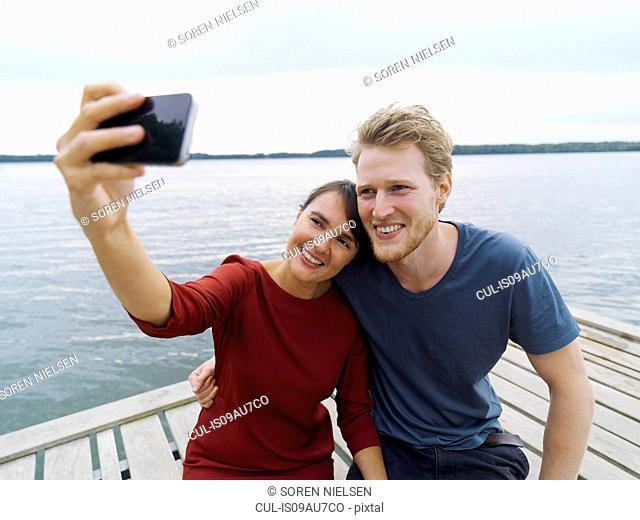 Couple on pier side by side using smartphone to take selfie smiling, Copenhagen, Denmark
