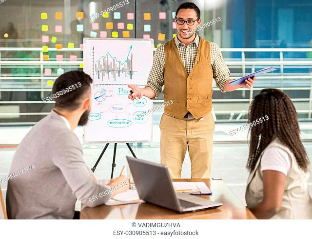 Young talented man showing to his colleagues new business strategy