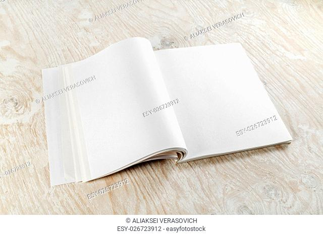 Photo of bank opened booklet on light wooden background with soft shadows. For design presentations and portfolios