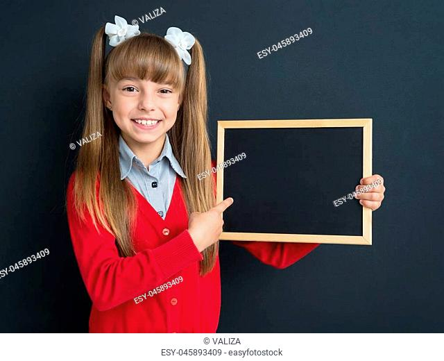 Portrait of happy girl 10-11 year old with small blackboard in front of a big chalkboard. Back to school concept