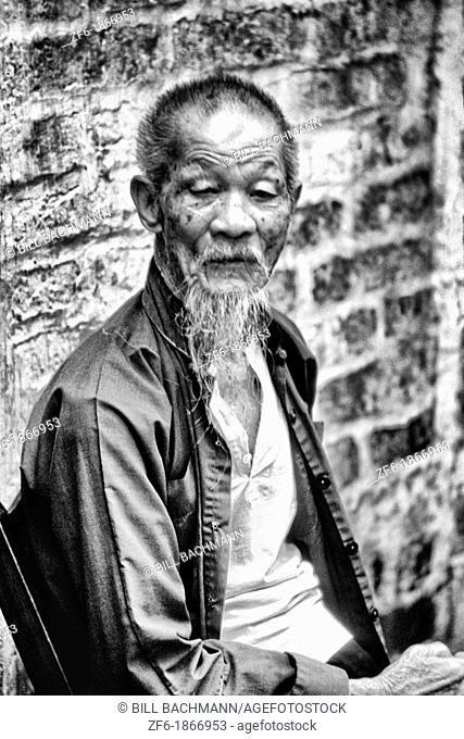 Old man in the old walled city of Kam Tin in the New Territories area of Hong Kong  This is a dying breed of local for tourists with black clothes