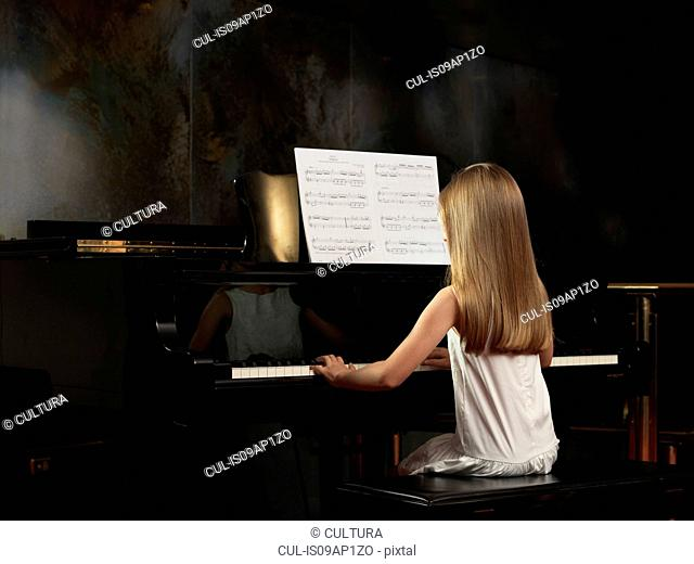 Rear view of girl playing piano on stage
