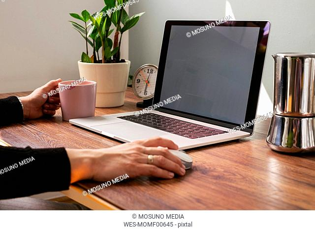 Woman working on laptop at home office, partial view
