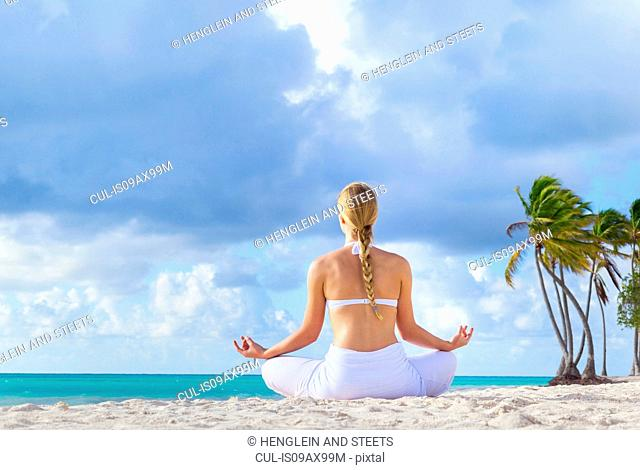 Rear view of young woman practising lotus pose on beach, Dominican Republic, The Caribbean