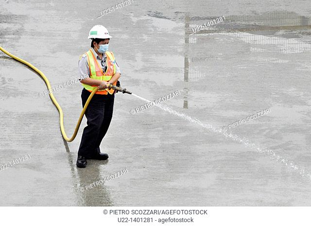 Hong Kong: a man at work watering the pavement by the construction of the new pier on Victoria Harbour, in Central