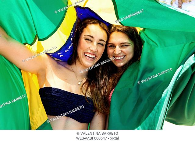 Two friends wearing beachwear playing with Brazilian flag