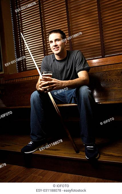 Young man holding billiards cue while hanging out at pub