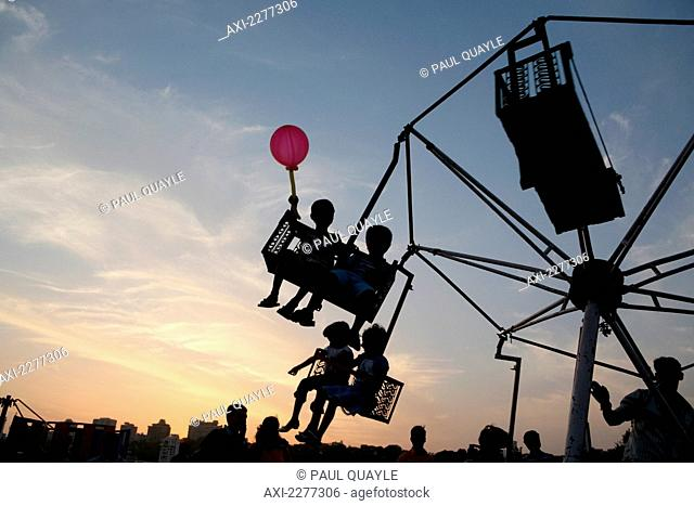 Silhouette of child with balloon and children on fair ground ride at sunset at Chowpatty Beach, new development on Malabar Hill in the background; Mumbai