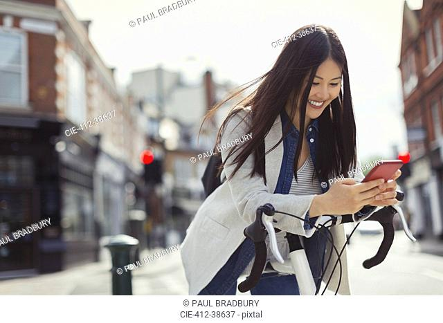 Smiling young woman commuting with bicycle, texting with cell phone on sunny urban street