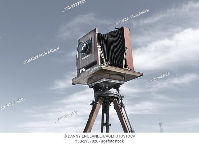 A classic vintage view camera on a tripod blue sky and clouds in the background