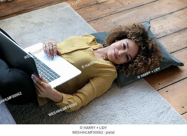 Smiling young woman lying on the floor at home with laptop