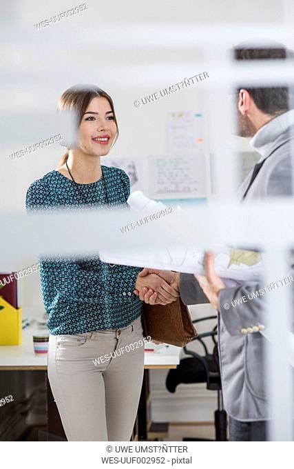Architect and woman shaking hands in office