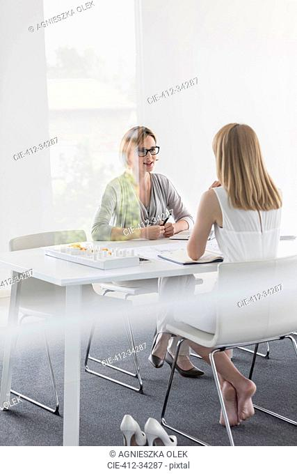 Barefoot female architect meeting with colleague in conference room
