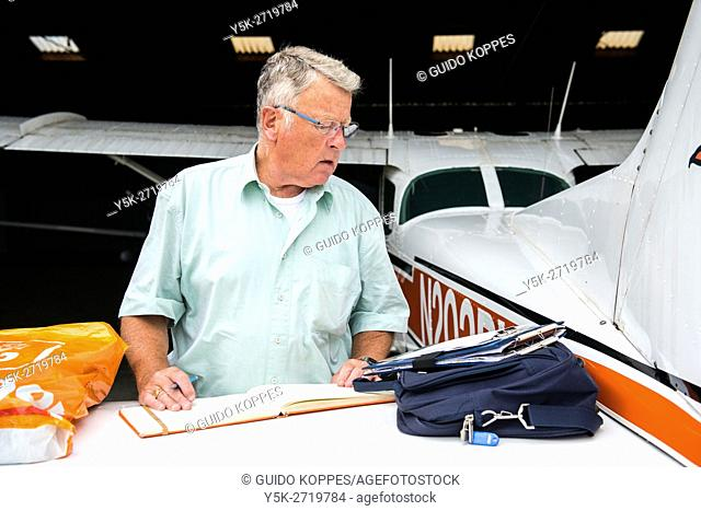 Seppe Airfield, Oudenbosch, Netherlands. Private pilot of a Cessna airplane filing his airplane log book post flight