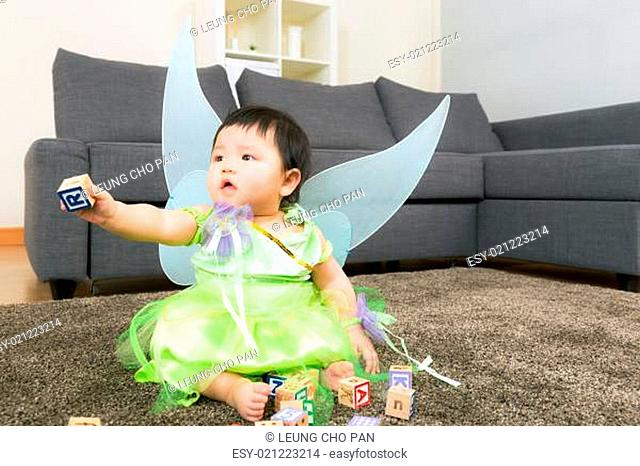 Asian baby girl with halloween party dressing and play toy block