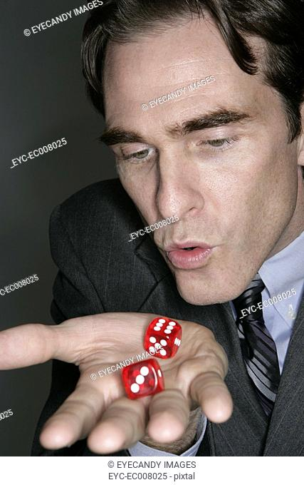 Businessman blowing dices