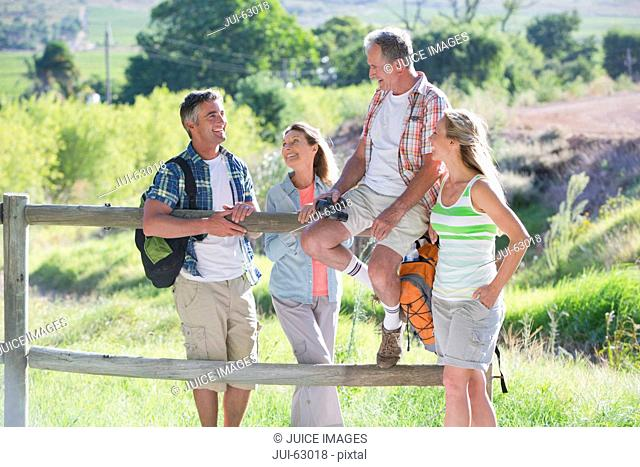Family resting on a fence in a rural setting
