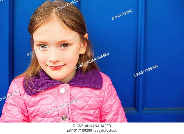 Close up portrait of a cute little girl of 7 years old, wering bright pink jacket, sitting against blue wall