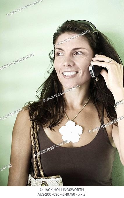 Close-up of a mid adult woman talking on a mobile phone and smiling