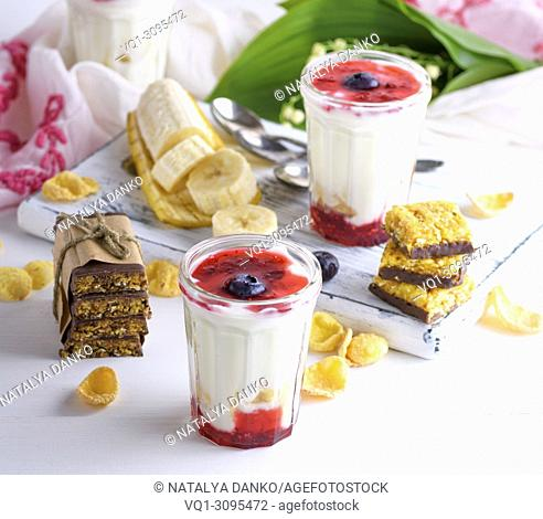 homemade yogurt in transparent glass with syrup and banana on a white wooden background