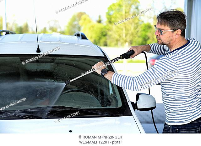 Man cleaning windscreen of his car