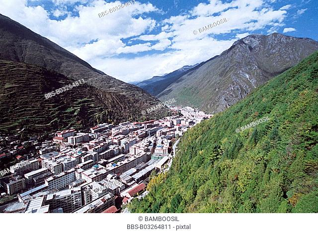 Cityscape with mountains against blue sky, To see Kangding County on Paoma Mountain, Kangding County, Ganzi State, Sichuan Province of People's Republic of...