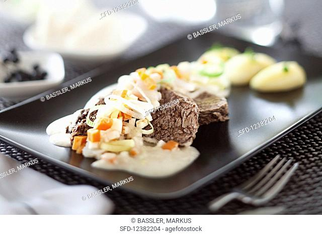 A joint of prime boiled beef with vegetables, horseradish sauce and potatoes