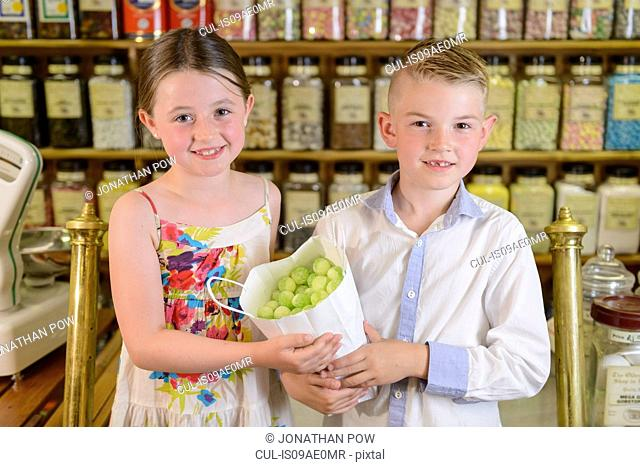 Children holding bag of confectionery