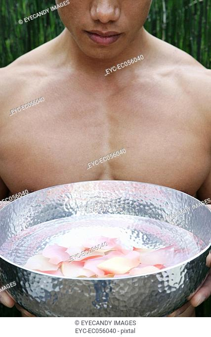 Close-up of a man holding a metal bowl filled with flower petals