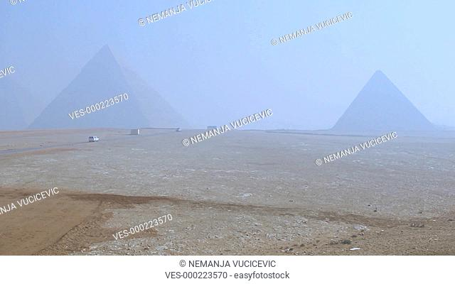 Shot of a road in the desert with tourist busses and cars taking people to the Great Pyramids of Giza