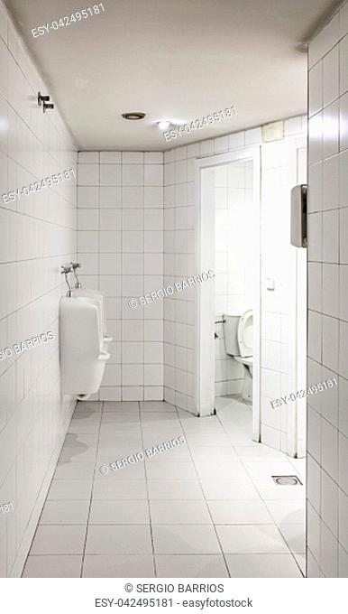Interior public bathroom in the city, detail of toilet for men, basic necessities