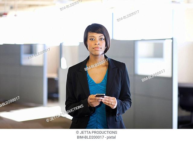 African American businesswoman holding cell phone in office