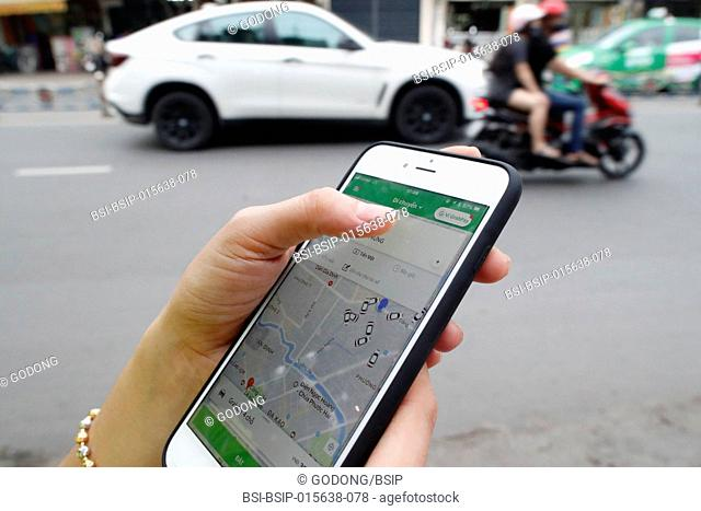 Woman using the Grab app on an Apple iPhone 6 Ho Chi Minh City. Vietnam