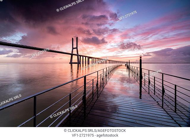 Sunrise colors the clouds reflected in Tagus River and frame the Vasco da Gama bridge in Lisbon Portugal Europe