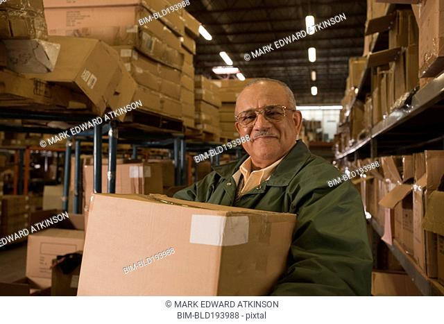 Mixed race man carrying box in warehouse