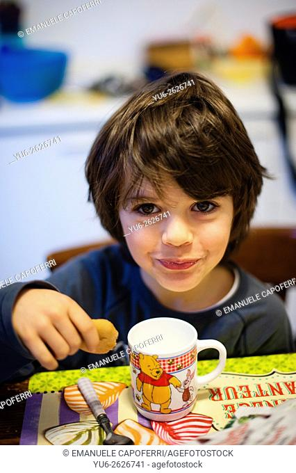 Child eats milk with breakfast biscuits