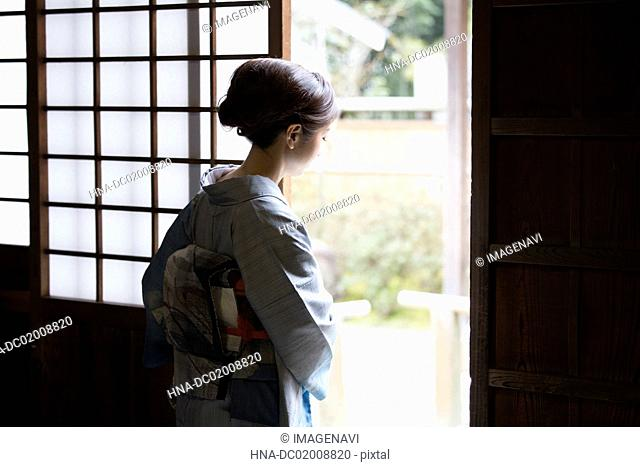 Young Japanese woman in kimono opening door