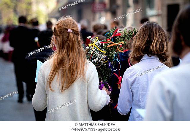 Children carrying self-made palm leaves walk through the historic district near the Frauenkirche (Cathedral of Our Dear Lady) during a PalmSunday procession in...