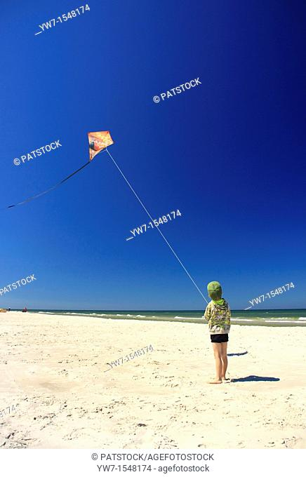 5 year old boy flying his kite on a beach