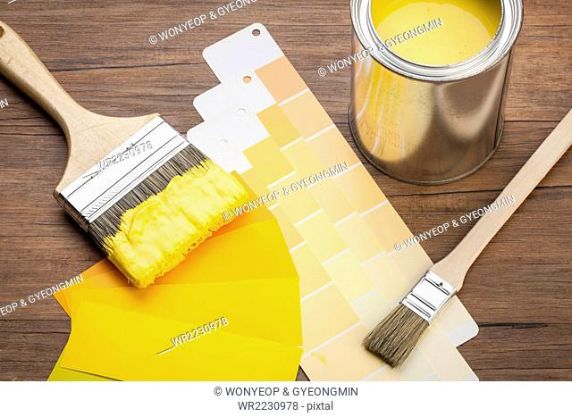 High angle of yellow paint and paint brush dipped in yellow paint with yellow color schemes on wood background