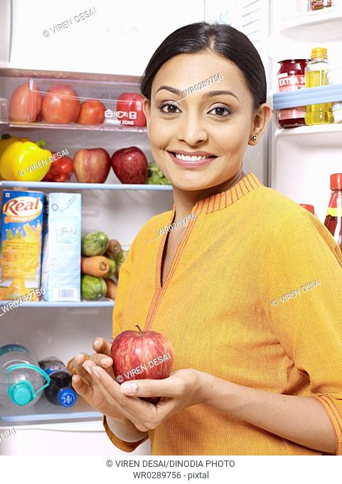Young lady kept red apple in hand palm standing at open refrigerator MR702U