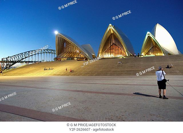 People relaxing in Sydney Opera House forecourt at dusk, with Harbour Bridge in the background